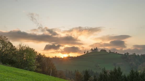Cover Image for Timelapse View of the Hills, Colorful Forest and the Sv Sobota Church. Slovenia Sunset in Autumn