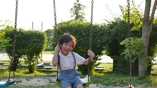 Cute Asian Child Having Fun On Swing In The Park Slow Motion