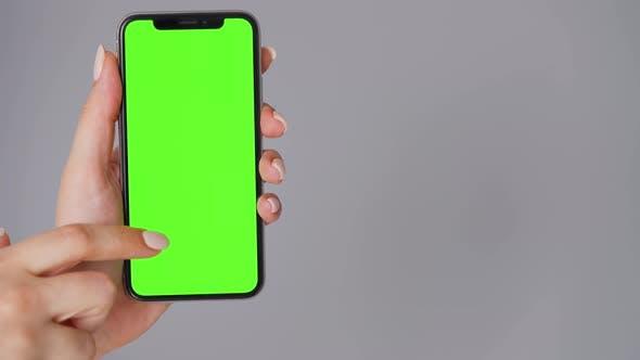 Weibliche Hände mit einem Smartphone mit einem grünen Bildschirm auf einem grauen Hintergrund. Chroma-Key.