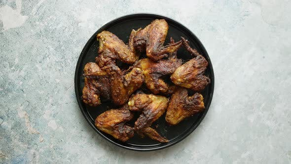 Thumbnail for Grilled Chicken Wings on a Black Ceramic Plate. Placed on a Stone