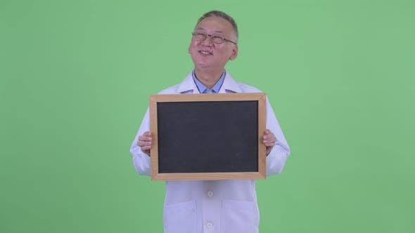 Thumbnail for Happy Mature Japanese Man Doctor Thinking While Holding Blackboard