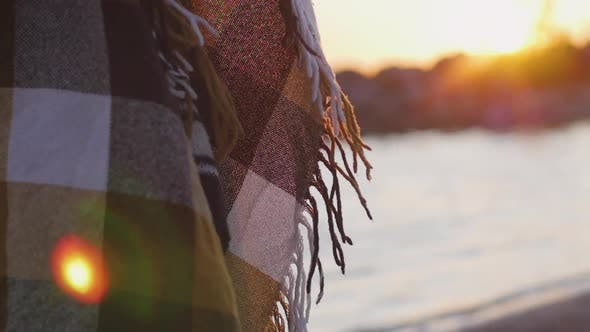 Thumbnail for Plaid Plaid auf dem Hintergrund des Sonnenuntergangs am Strand. Mädchen eingehüllt in eine Decke am Strand