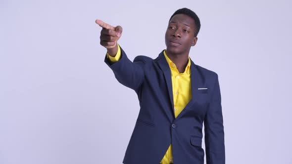Young Happy African Businessman Directing and Pointing Finger