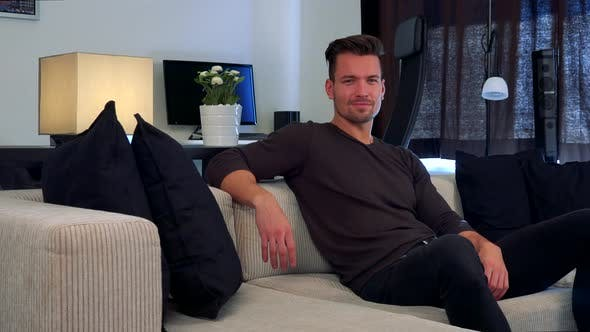 Thumbnail for A Man Sits on a Couch, Looks at Something Off the Camera and Eventually Looks and Smiles at Camera