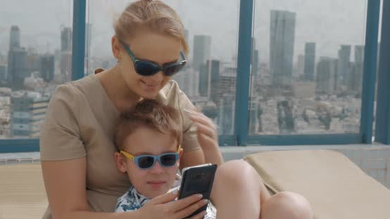 Thumbnail for Mom and Child Using Mobile When Relaxing on Hotel Rooftop in Tel Aviv, Israel