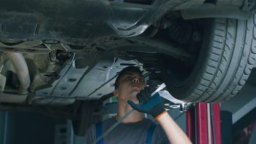 Young Mechaniker Prüfung Auto in Wartung Service, Herstellung Suspension Test in der Garage