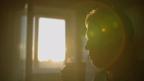 Silhouette of a Man with a Mug of Hot Fresh Steam Coffee Over a Mug Sun Flare Camera Movement