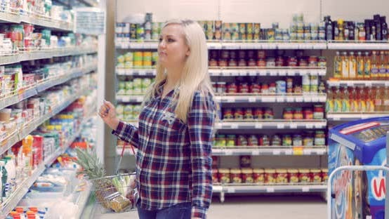 Attractive Woman Buying Dairy Produce in a Supermarket