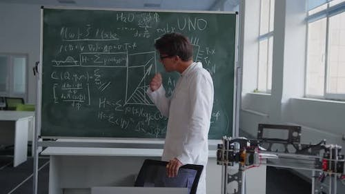 Teacher Looks on the Blackboard and That Looks on the Camera