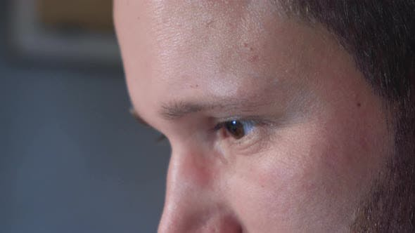 Close-up of the eyes and face of a young man working at a computer on a Black Background.