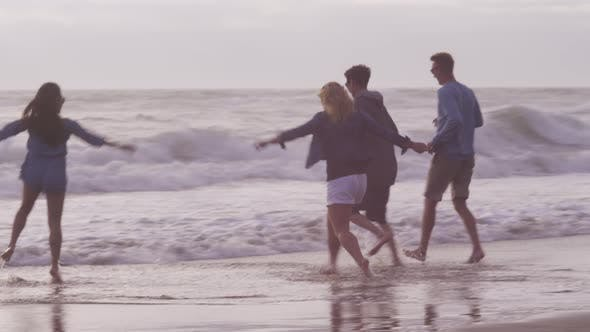 Thumbnail for Group of friends at beach running together