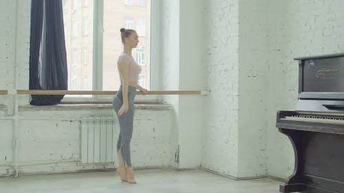 Ballet Dancers Practicing Relevelent at Barre