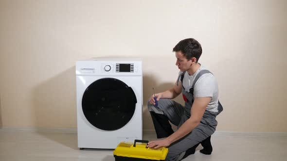 Serviceman with Toolbox Comes To Check Washing Machine
