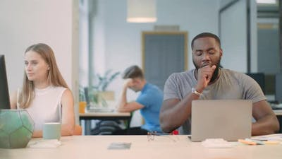 Black Man Yawning at Workplace
