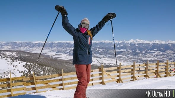 4K Happy Skier Cheering in Success at the top of a Ski Resort Mountain Range in Slow Motion