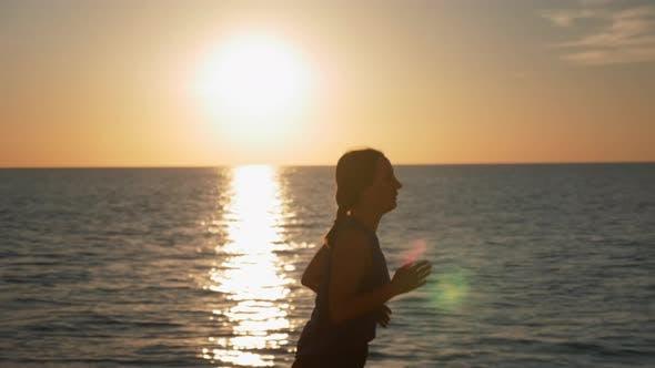Thumbnail for Konzentrierte brünette Frau läuft bei Sonnenaufgang und macht Morgengymnastik am Meer.