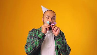 Happy African American Male in Party Cone Blowing Party Blower Against Yellow Background