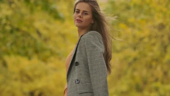 Thumbnail for Back View of a Young Caucasian Woman in Checkered Jacket Standing in the Autumn Park