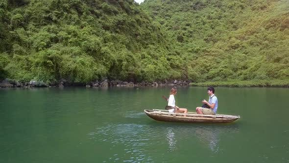 Thumbnail for Drone Shows Girl and Man Rowing on Boat on Lake By Ha Long Bay