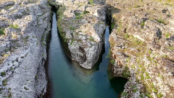 Fork of a narrow mountain river flowing through rocky landscape. Stream bed cut deep into rock.
