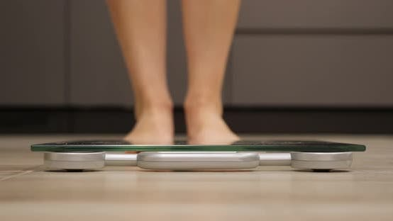 Thumbnail for Female feet step on weighing scales. Weight loss concept