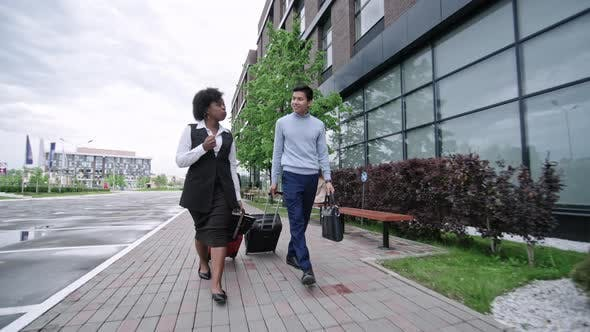 Thumbnail for Business Travelers Walking with Suitcases in Downtown