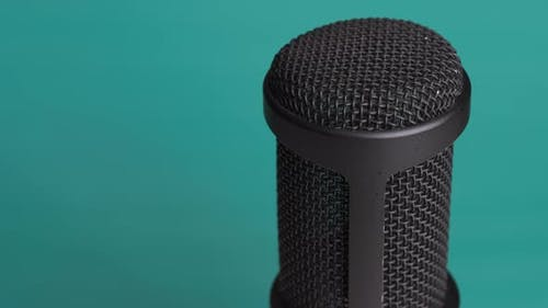Studio Condenser Microphone Rotates on Blue Background with Place for Text