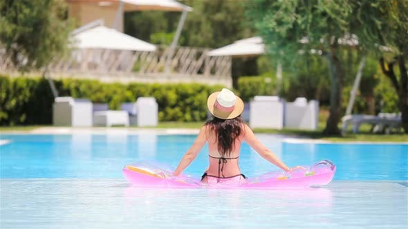 Thumbnail for Young Woman Relaxing in Swimming Pool