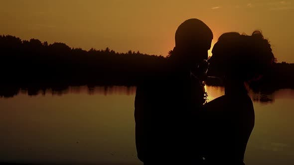 Two Young People Hugging Against the Backdrop of a Sunset By the River Closeup Slow Motion
