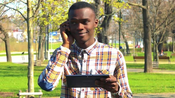 Thumbnail for A Young Black Man Talks on a Smartphone While Looking at a Tablet in a Park on a Sunny Day