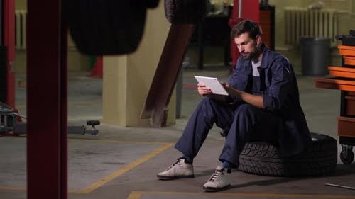 Auto Mechanic Using Tablet To Order Car Parts