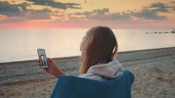 Young Woman Making Video Call with Smartphone on the Seashore