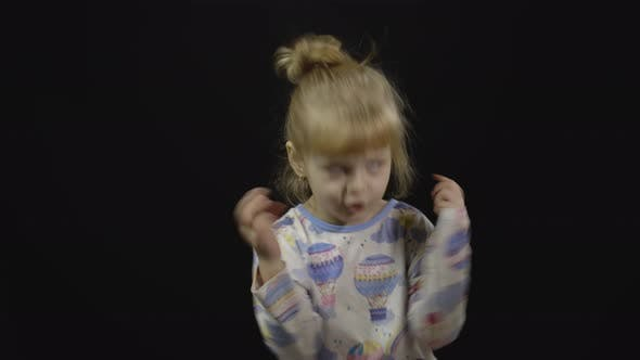 Thumbnail for Little Girl in Pajama Is Dancing and Playing on Black Background