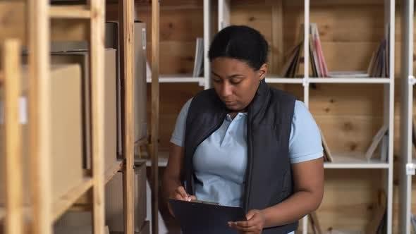 Thumbnail for Black Female Post Office Clerk Checking Parcels on Racks