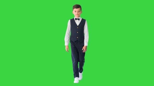 Kleiner Junge mit Weste und Fliege, der geradeaus auf grünem Bildschirm schaut, Chroma Key
