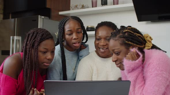 African Mom Watching Family Video with Daughters