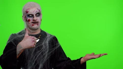 Scary Wounded Halloween Zombie Undead Man Showing Thumbs Up and Pointing at Right on Blank Space