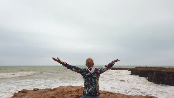 Girl Raises Her Hands Up While Standing with Her Back on the Seashore During a Storm
