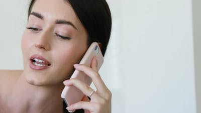 gorgeous young woman listens to pink smartphone