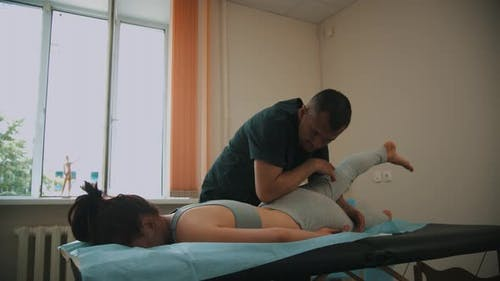 Woman Having an Osteopathic Treatment - the Doctor Warming Up the Leg of Young Woman