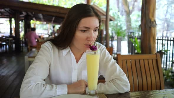Young Woman Drinks a Fruit Cocktail in a Cafe