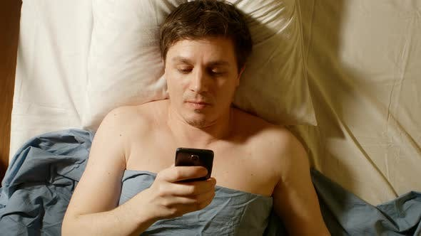 Thumbnail for Caucasian Young Man Types By Mobile Phone In A Bed