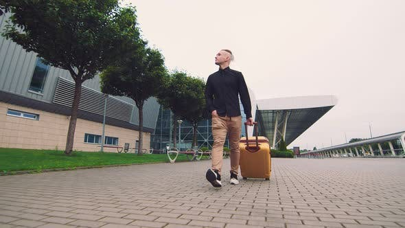 Thumbnail for Male Businessman Returning From a Business Trip. A Man Walks Holding Luggage in His Hand.