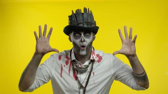 Sinister Man with Horrible Halloween Skeleton Makeup Making Faces, Looking at Camera Trying To Scare