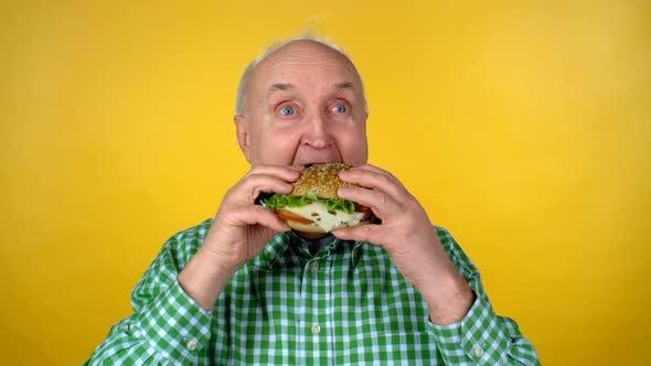 Thumbnail for Hungry Elderly Man Eating Hamburger