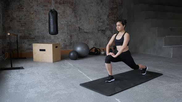 Young fit sporty brunette girl with black top, black leggings does exercises on mat in gym