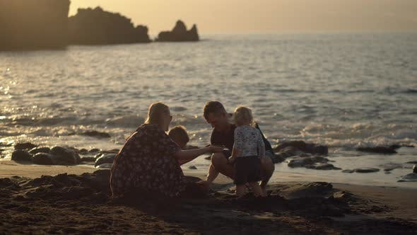 Thumbnail for Family of Four Playing in Sand on the Evening Seashore