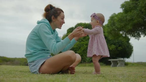 Happy Little Baby Girl Playing Together with Her Mother Outdoor in the Park Adorable Baby Lifestyle