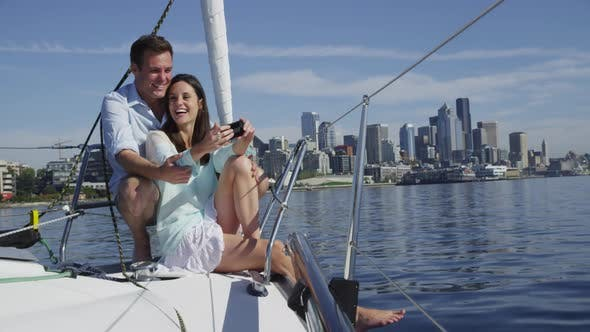 Young couple on sailboat together using cell phone. Shot on RED EPIC for high quality 4K, UHD, Ultra