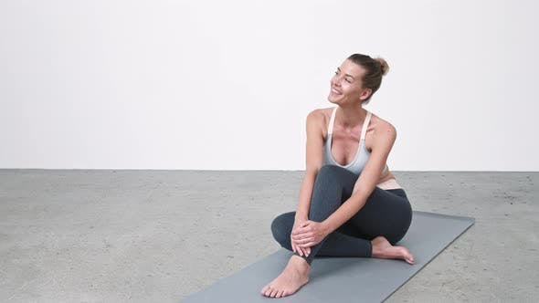 Woman Smiling on Exercise Mat